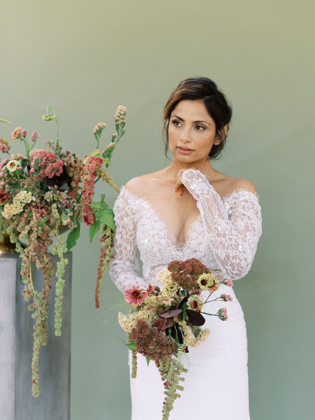 bride holding bouquet standing near flowers