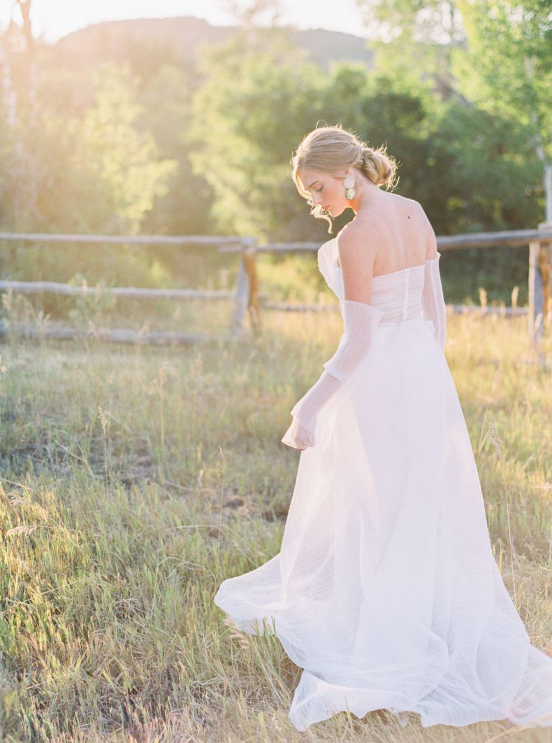 bride in grass field with hair in curled bun and earrings