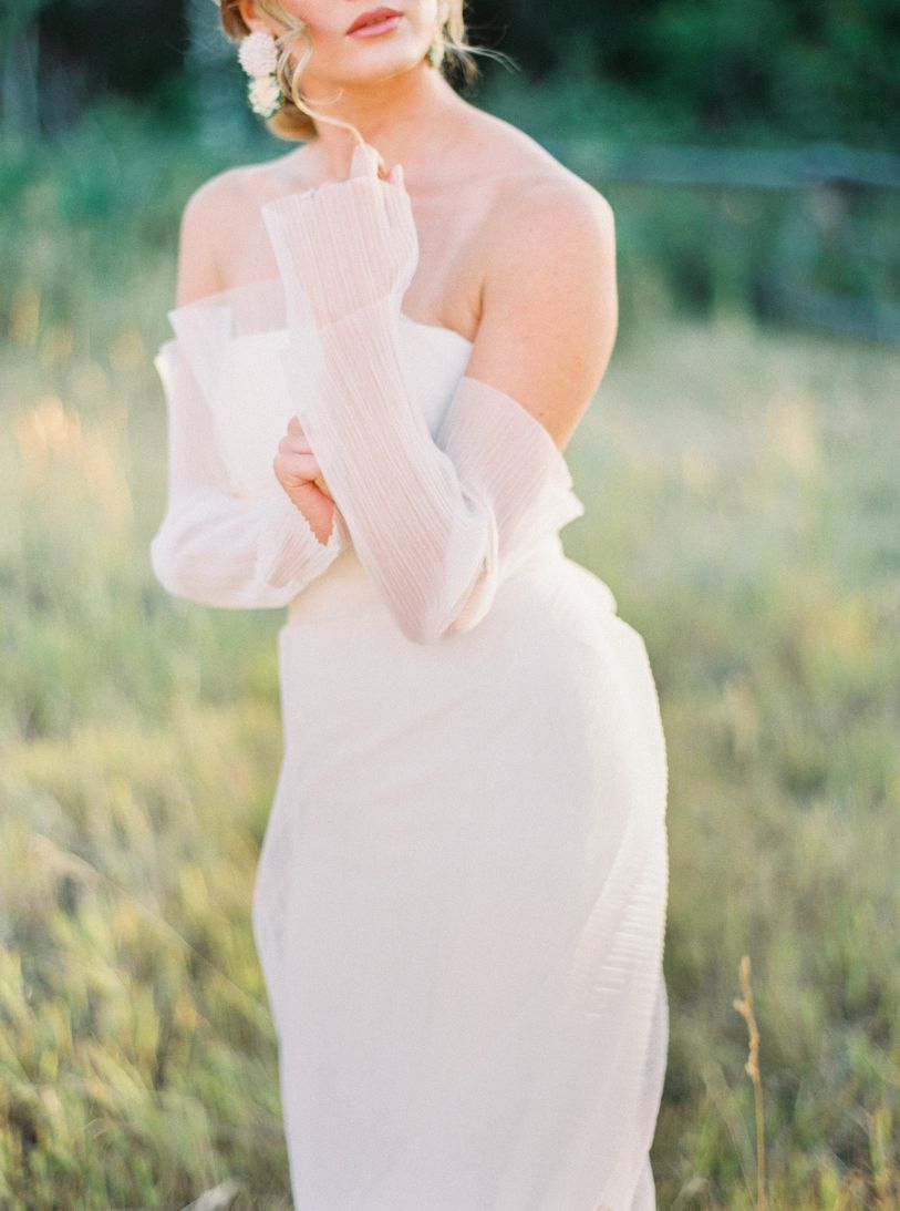 bride in grass field with pink red lipstick