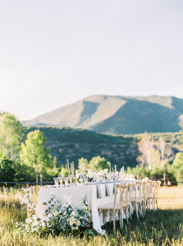 wedding table in grass field and mountain backdrop