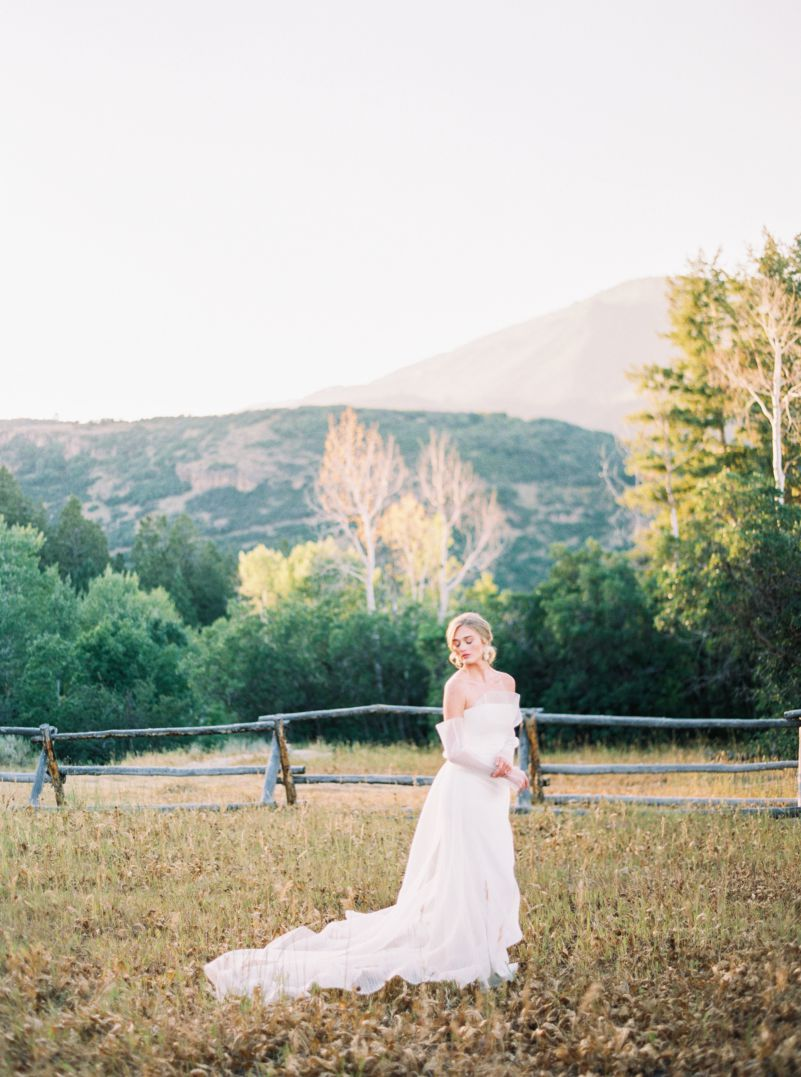 bride in white wedding gown in grassy field with mountains