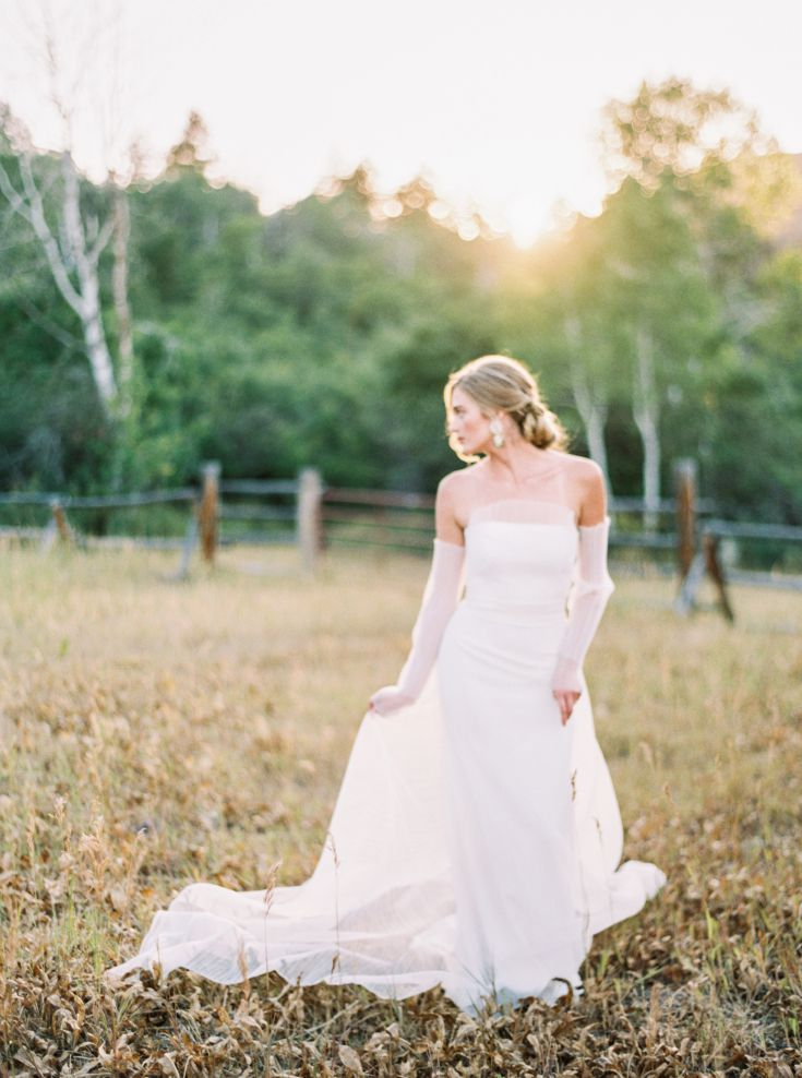 bride with natural makeup and hair posing in grass field