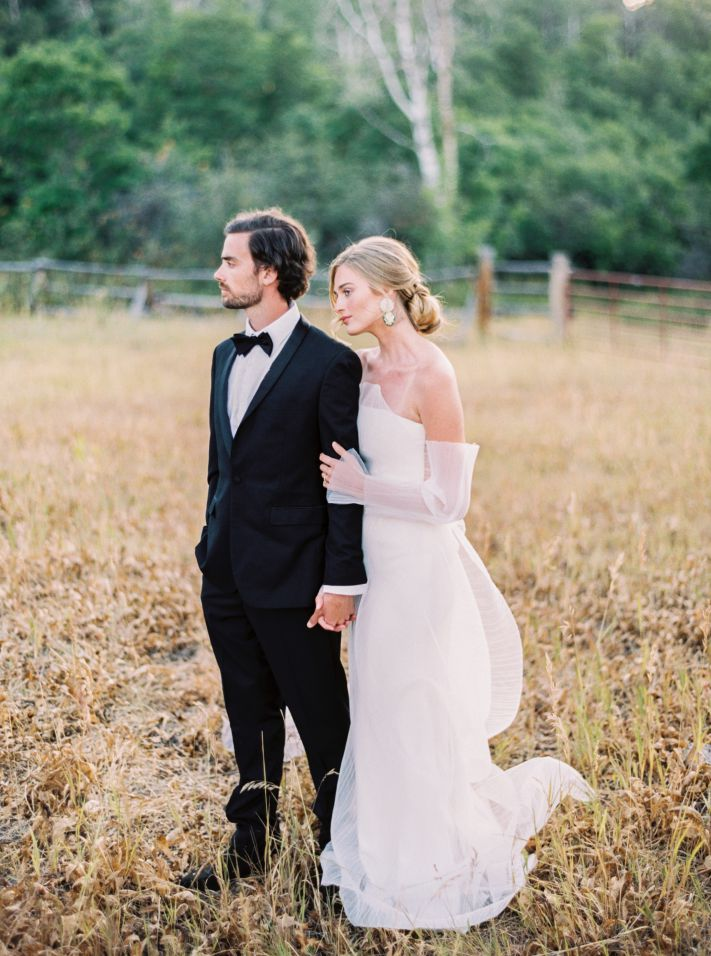bride and groom posing in grass field