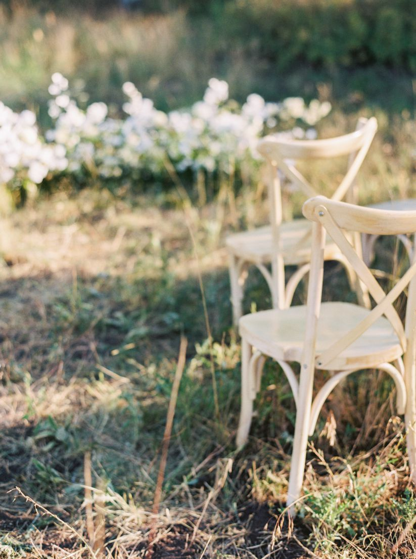 wedding chairs among woods and grass