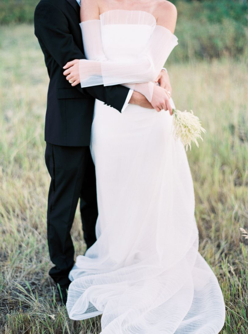 bride and groom embracing in grass field