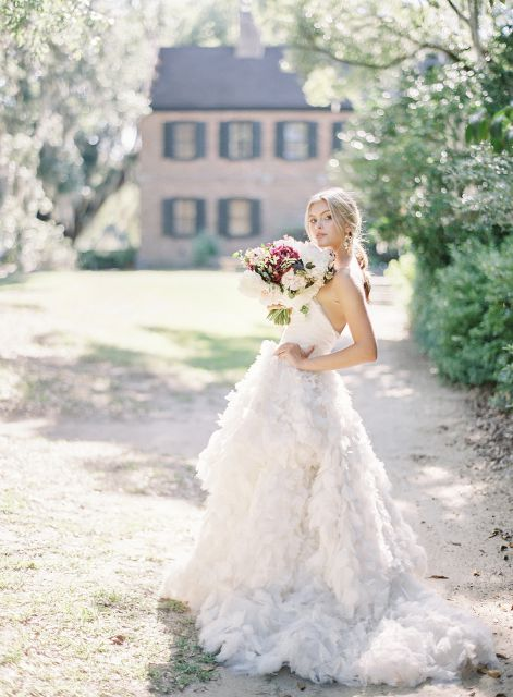 bride holding bouquet standing in grass field