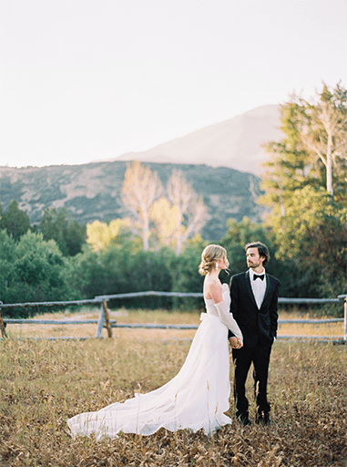 bride and groom standing in beautiful mountain scene