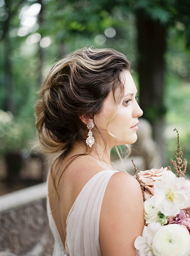 beautiful updo on bride standing in the woods