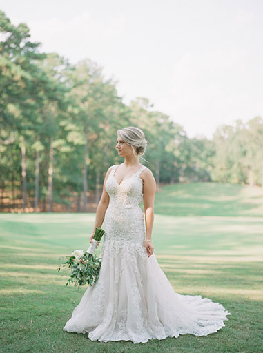 bride holding bouqet standing in grassy field