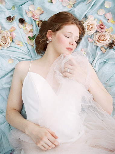 redhead bride laying on blue silk with flowers scattered nearby