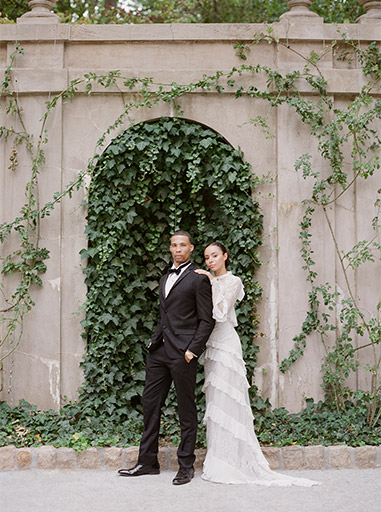 bride and groom posing in front of wall with vines