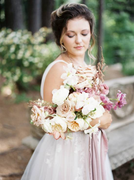 bride holding brirdal bouquet in the woods