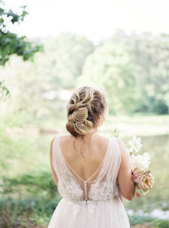 bride with updo facing off at a lake