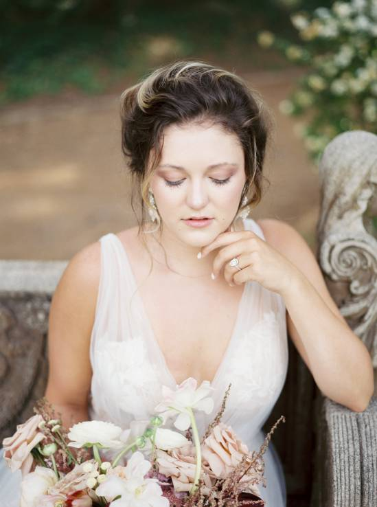 bride in white dress sitting on a bench