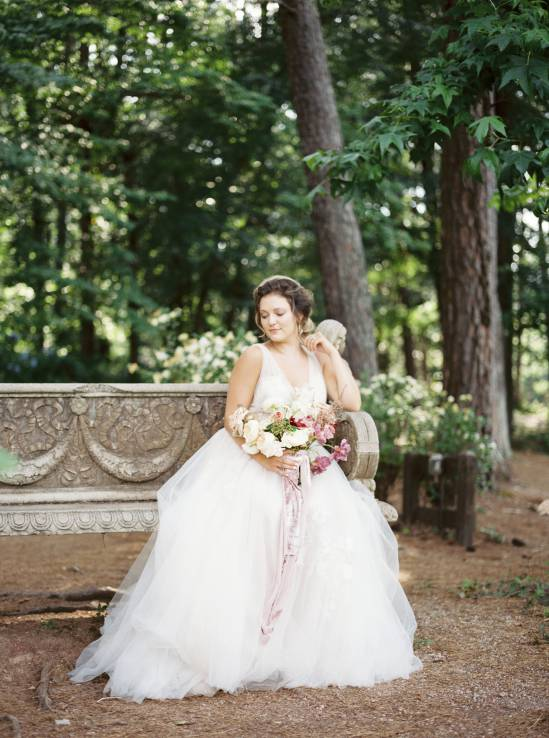 bride resting on a bench in the woods