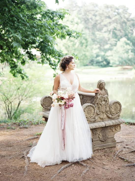 bride leaning on bench overlooking a lake
