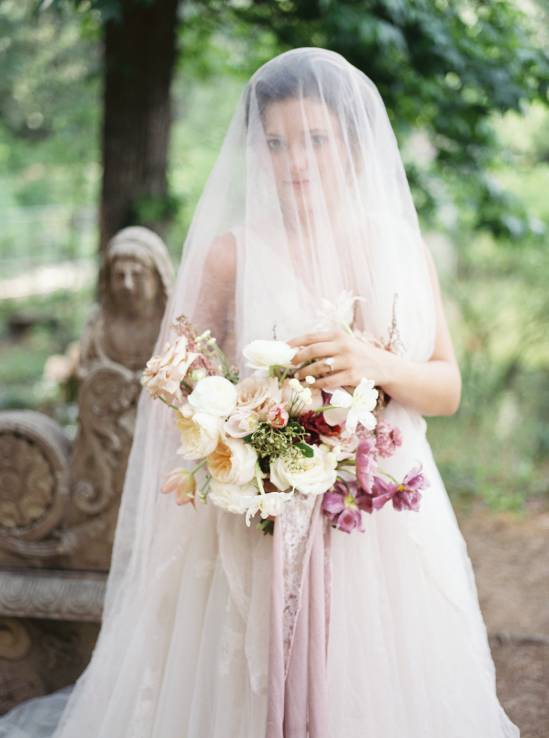 bride draped in white wedding veil holding bouquet