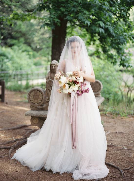 bride draped in wedding veil in front of a lake