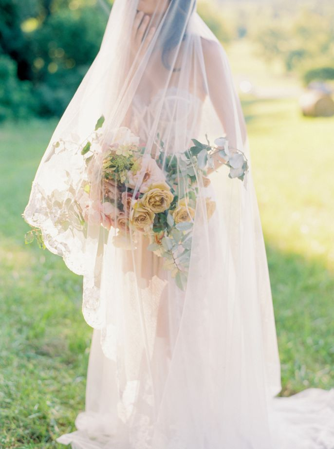 wedding portrait bride with veil draping over face and flowers