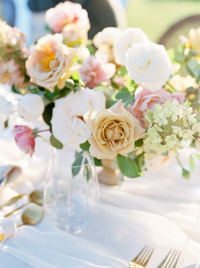 wedding table with colorful flowers and white tablecloth