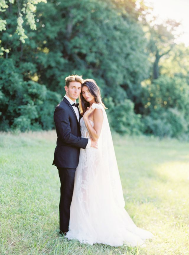 bride and groom posing in grassy field