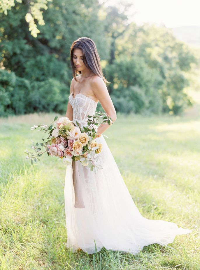 bride in grassy field with bouqet