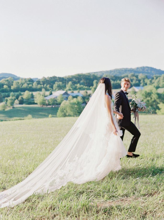 groom leading the bride through field