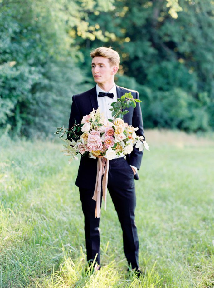 groom in navy suit posing with bridal bouqet