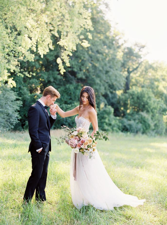 groom kissing bride's hand in grassy field