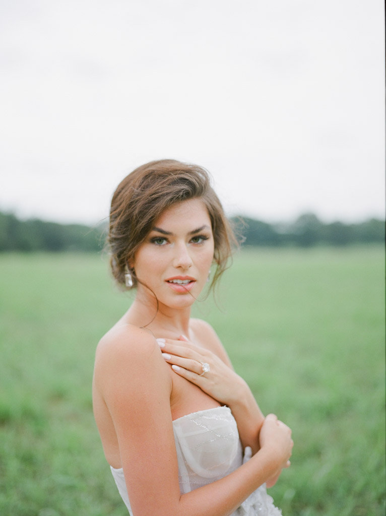 bride looking at camera in grassy field