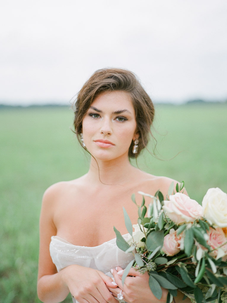 bride with bouquet in grassy field